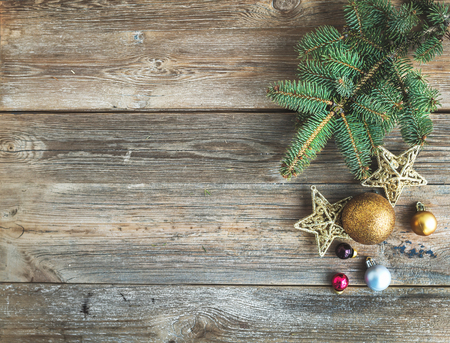 Foto de Christmas or New Year rustic wooden background with toy decorations and fur tree branch, top view, copy space - Imagen libre de derechos