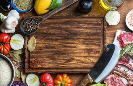 Foto de Ingredients for cooking healthy meat dinner. Raw uncooked lamb chops with vegetables, rice, herbs and spices over rustic wooden background, dark chopping board in center with copy space. Top view - Imagen libre de derechos