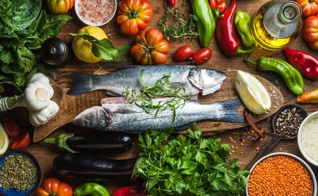 Foto de Raw uncooked seabass fish with vegetables, grains, herbs and spices on chopping board over rustic wooden background, top view - Imagen libre de derechos