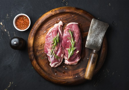 Photo pour Raw uncooked poultry meat cut. Duck breast with rosemary, spices and butcher cleaver on dark wooden tray over black wooden background, top view - image libre de droit