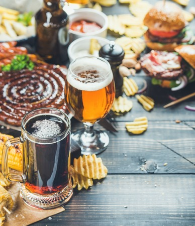 Photo pour Beer and snack set. Oktoberfest food frame concept. Variety of beers, grilled sausages, burgers, potato chips and sauces on dark wooden scorched background. Selective focus, copy space - image libre de droit