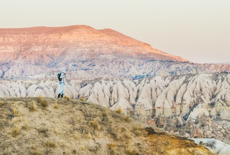 Young woman traveller looking aside and hiking in the mountains among natural rocks of Cappadocia, Central Turkey. Concept of adventures and travel lifestyle