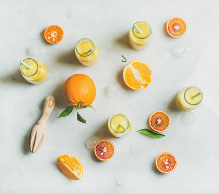 Foto de Healthy yellow smoothie with citrus fruit, ginger and ice in glass bottles over light marble table background, top view. Clean eating, vegan, vegetarian, detox, dieting, weight loss food concept - Imagen libre de derechos
