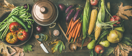 Foto de Fall healthy cooking background. Ingredients for Thanksgiving day dinner. Flat-lay of beans, corn corn, carrot, tomatoes, eggplants, fruits and fallen leaves over wooden table, top view - Imagen libre de derechos