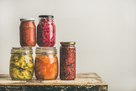 Foto de Autumn seasonal pickled or fermented colorful vegetables in glass jars placed in stack over vintage kitchen drawer, white wall background, copy space. Fall home food preserving or canning - Imagen libre de derechos