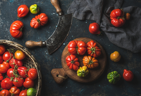 Foto de Fresh colorful ripe Fall heirloom tomatoes in basket and on wooden board, herb chopper knife for cooking over grunge dark plywood background, top view. Harvest vegetable cooking conception. - Imagen libre de derechos