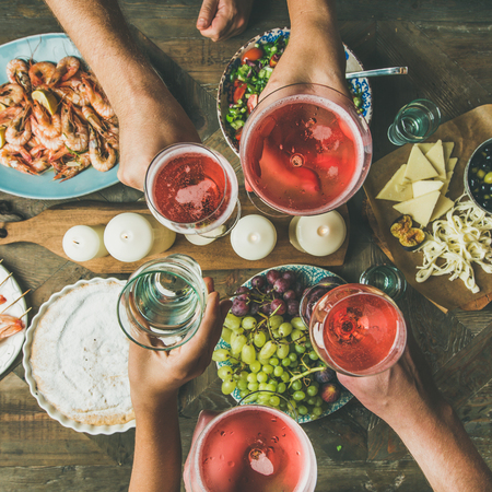 Photo pour Holiday celebration table setting with food. Flat-lay of friends hands eating and drinking together. Top view of people having party, gathering, celebrating with rose champaign, square crop - image libre de droit
