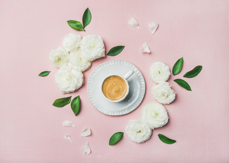 Photo for Spring morning concept. Flat-lay of cup of freshly brewed coffee surrounded with white ranunculus flowers and petals over light pink pastel background, top view - Royalty Free Image