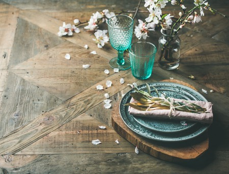 Foto de Spring Easter holiday Table setting. Tender almond blossom flowers on branches, plates, glasses and cutlery over vintage wooden table, selective focus, copy space. - Imagen libre de derechos