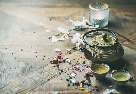 Photo for Traditional Asian tea ceremony arrangement. Iron teapot, cups, dried rose buds and candles over wooden table background, selective focus, copy space - Royalty Free Image