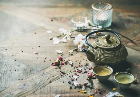 Photo pour Traditional Asian tea ceremony arrangement. Iron teapot, cups, dried rose buds and candles over wooden table background, selective focus, copy space - image libre de droit