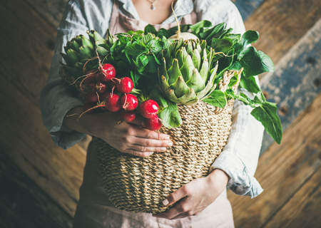Photo pour Female farmer in linen apron holding basket of fresh garden vegetables and greens in her hands, rustic wooden barn wall at background, horizontal composition. Local market or organic produce concept - image libre de droit