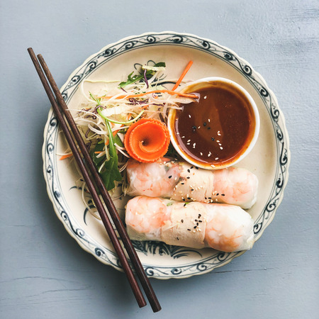 Photo for Asian style dinner. Flat-lay of summer rice paper rolls with shrimp and teriyaki sauce in bowl over blue table, top view, copy space, square crop. Chinese cuisine - Royalty Free Image