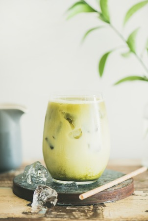 Foto de Iced matcha latte drink in glass, white wall and plant branches at background, copy space, close-up. Summer refreshing beverage cold drink - Imagen libre de derechos