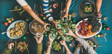 Photo pour Company of friends or family gathering for Christmas or New Year party dinner at festive table. Flat-lay of human hands holding glasses with drinks, feasting and celebrating holiday together, top view - image libre de droit
