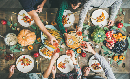 Photo pour Vegan or vegetarian Thanksgiving, Friendsgiving holiday celebration. Flat-lay of friends eating and clinking glasses at Thanksgiving Day table with pumpkin pie, vegetables, fruit and wine, top view - image libre de droit