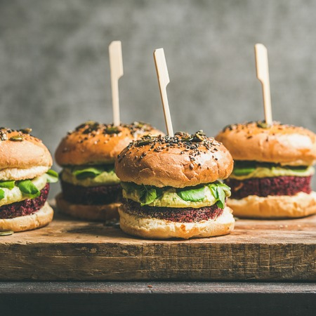 Photo for Flat-lay of healthy vegan burgers with quinoa beetroot patties, avocado cream and green sprouts on wooden board, grey wall at background, square crop. Vegetarian, clean eating, alkiline diet food - Royalty Free Image