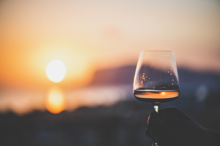 Foto de Man's hand holding glass of rose wine and with sea and beautiful sunset at background, close-up, horizontal composition. Summer evening relaxed mood concept - Imagen libre de derechos