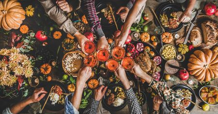 Photo for Family celebrating Thanksgiving day. Flat-lay of feasting peoples hands clinking glasses with rose wine over Friendsgiving table with traditional Fall food, roasted turkey, pumpkin pie, top view - Royalty Free Image