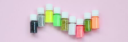 Photo for Colorful glitters lies on pastel pink background. Many round jars with multi-colored bright sparkles for nail polish. Sparkling sequins - Royalty Free Image