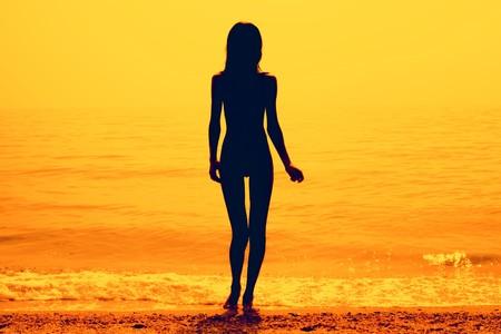 Foto de Silhouette of a skinny young girl walking along the beach - Imagen libre de derechos