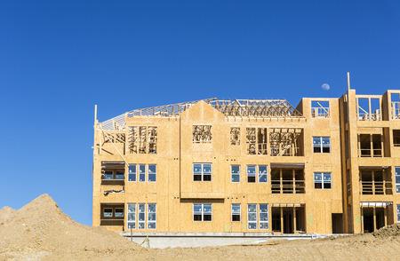 Photo pour Big multifamily housing under construction against blue sky - image libre de droit