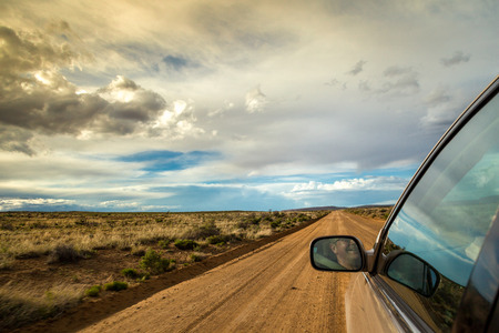 Photo for Smiling man driving through wilderness on straight dirt road - Royalty Free Image