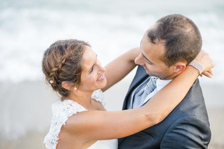 Foto de Bride and groom hugging each other on the beach - Imagen libre de derechos