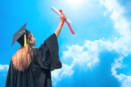 happy graduate showing certificated in hand with sky background
