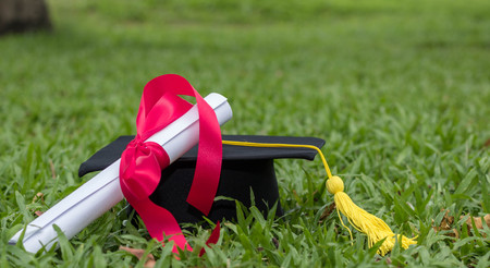 Foto de graduate hat and certificated in the garden - Imagen libre de derechos