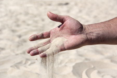 Photo for sand flowing through the fingers of the palm as a symbol of the passing time - Royalty Free Image