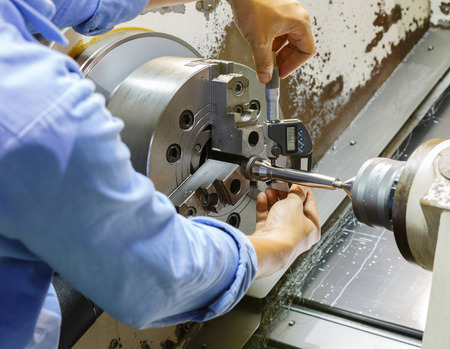 Photo pour worker measuring cnc turning part ny micro meter - image libre de droit