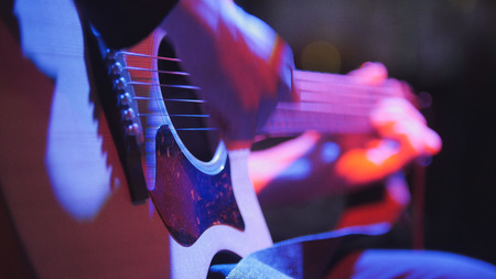 Photo pour Musician in night club - guitarist plays blues acoustic guitar, extremely close up, telephoto - image libre de droit