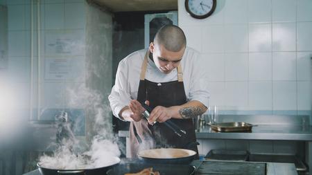 Foto de The cook adds spices to food - Imagen libre de derechos