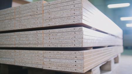 Foto de Stack of wood particleboard panels on the warehouse or factory - Imagen libre de derechos