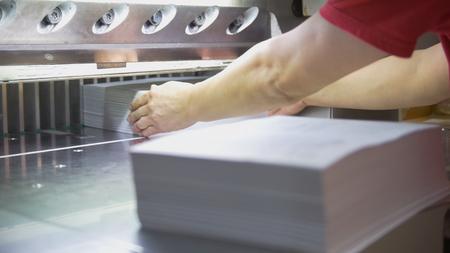 Foto de Hands of worker takes away reams of paper from cutting maschine - Imagen libre de derechos