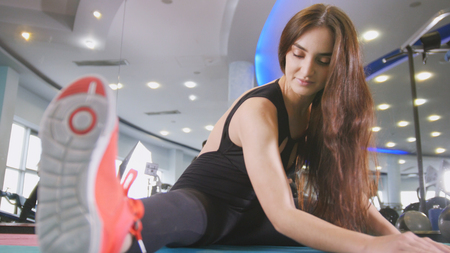 Photo for Straching in the gym - young woma exercising healthy lifestyle in fitness studio - Royalty Free Image