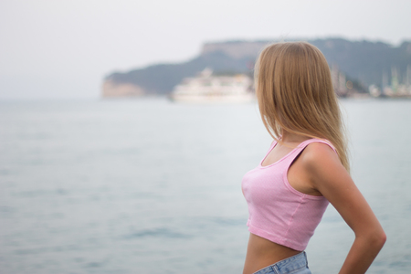 Photo for Portrait of unrecognizable young blonde woman looking at mountain by the sea - Royalty Free Image