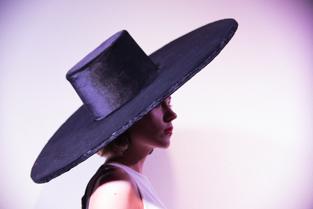 Photo for Young attractive woman standing on the background of a white wall in big hat - Royalty Free Image