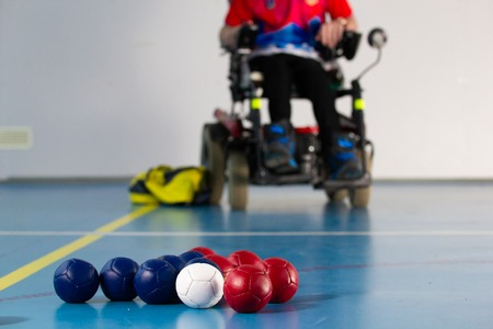 Foto de Boccia. A disabled sportsman sitting in a wheelchair. Close up of little balls for playing boccia. Tricolor. - Imagen libre de derechos