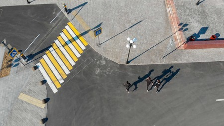 Photo pour Aerial view of urban streets. Three men walking on the road - image libre de droit