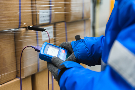 Foto de Hand of worker using thermometer to temperature measurement in the goods boxes with ready meals after import in the cold room or warehouse for keep temperature room - Imagen libre de derechos