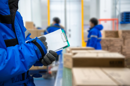 Foto de Closeup shooting hand of worker with clipboard checking goods in freezing room or warehouse - Imagen libre de derechos