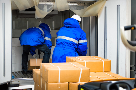 Foto de Manual worker working with package boxes for transport by pickup at gates for goods in loading area from warehouse to be processed export to customer - Imagen libre de derechos