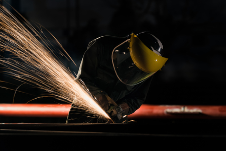 Foto de Worker with the face guard to electric wheel grinding on steel structure in factory - Imagen libre de derechos