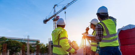 Foto de Construction engineers discussion with architects at construction site or building site of highrise building with Surveying for making contour plans is a graphical representation of the lay in land. - Imagen libre de derechos