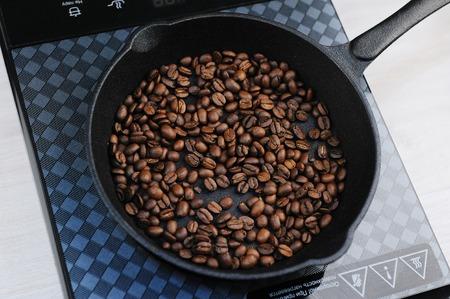 Foto de Home roast coffee in a cast iron pan. Induction cooker top view - Imagen libre de derechos