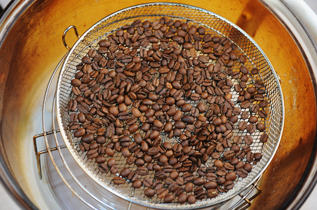 Foto de Freshly roasted coffee beans in aerogrill. Top view. Home roasting - Imagen libre de derechos
