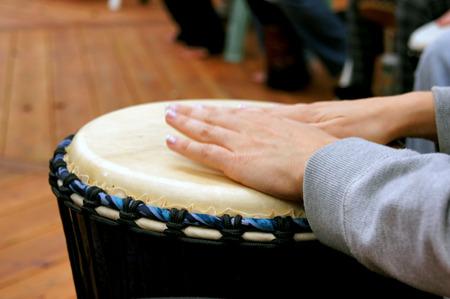 Foto de Close up of woman's hands as she drums in a drum circle. - Imagen libre de derechos