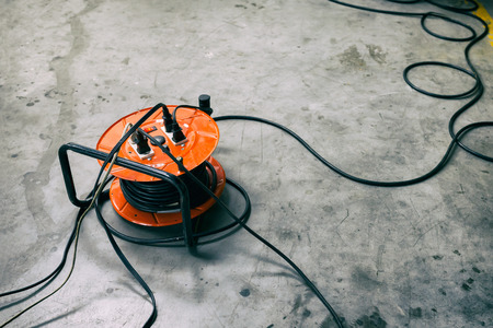 Photo for Cable reel Orange color Be plugged with Black Cable Wire Placed on the floor. - Royalty Free Image